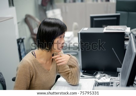 Single mature Asian woman working in office and looking at computer screen.
