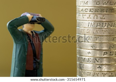 Single miniature model looks through binoculars into a pile of British pound coins - stock photo