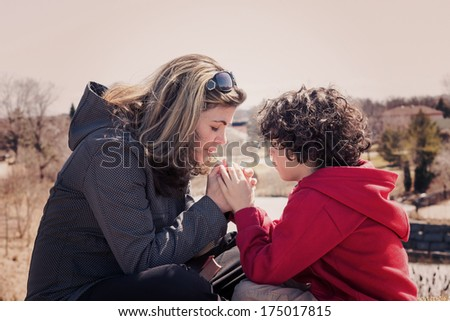 Single mother and her son having a devotional outdoors. Praying for the city with instagramesque effect - stock photo