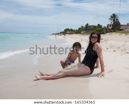 Single mother enjoying her son in a tropical beach. Both playing with the white sand. Blue water beach and family having fun. Tropical paradise in the Caribbean. - stock photo