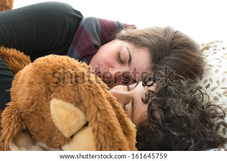 Single mother sleeping with her son and a teddy bear. Candid picture of a small family. Normal life at home. Hispanic family over white background. Isolated people sleeping. - stock photo