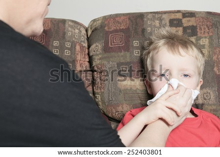 Single mother with son who suffers from a cold. She is helping him to blow his nose using white tissue paper - stock photo
