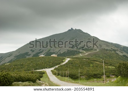 Single mountain and tourist route/path during summer cloudy and foggy day. - stock photo