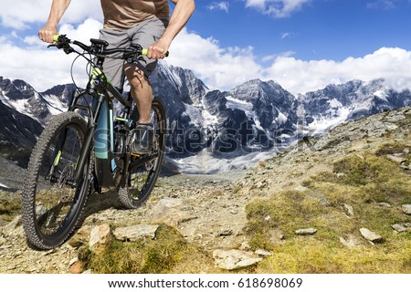 Single mountain bike rider on ebike rides up a steep mountain trail.