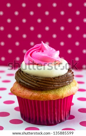 Single neapolitan frosted cupcake on pink polka tablecloth, and background - stock photo