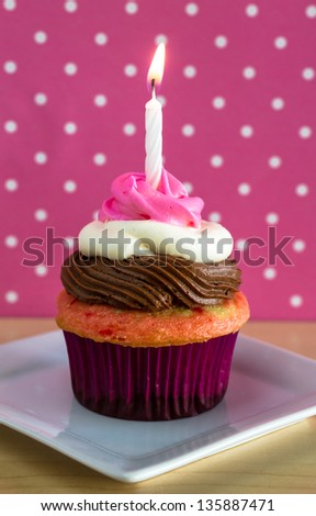Single neapolitan frosted cupcake on white plate and pink polka dot background, with one lit birthday candle