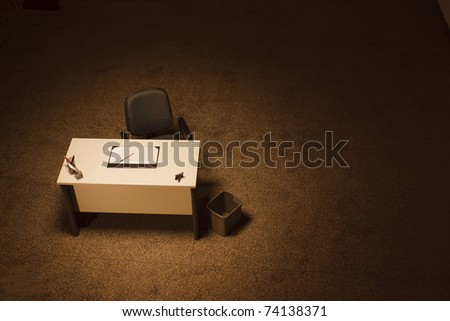 Single office desk in a empty room with dark grey office chair - stock photo