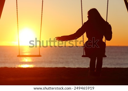 Single or divorced woman alone missing a boyfriend while swinging on the beach at sunset - stock photo