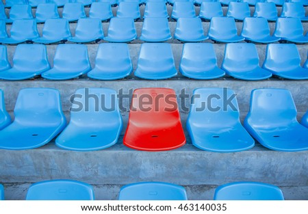 Single or one red seat or bench in the middle or center of blue chair in the football or soccer stadium.