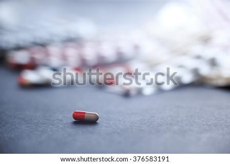 Single orange-white capsule. Single tablet on background with many medicine orange and white capsules. Background of orange tablets. Medications. Pills. Abstract pharmaceutics background. - stock photo