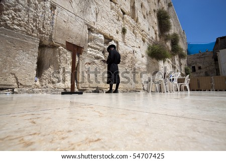 single orthodox man praying at the western wall in jerusalem - stock photo