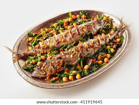 Single oval shaped silver platter full of two whole cooked mackerel fish stuffed with spices and garnished with beans and spinach - stock photo