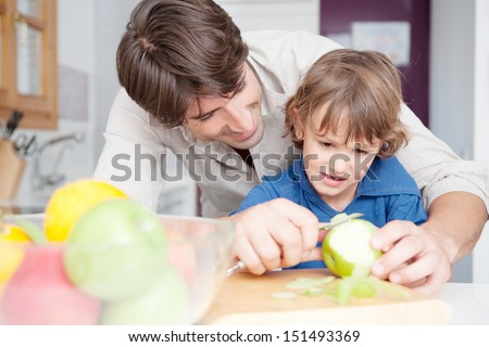 Single parent dad teaching his young son how to peel green apples standing by a kitchen counter at home, interior. - stock photo