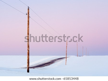 Single phase electrical power lines through an empty snow landscape against a pink sky. - stock photo