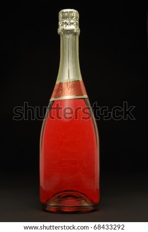 Single pink champagne bottle on black background - stock photo