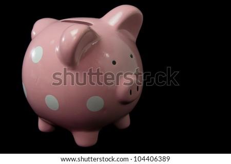 single Pink Polka Dot Piggy Bank on black background - stock photo