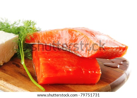 single pink salmon bit on a big wooden dish with white cheese