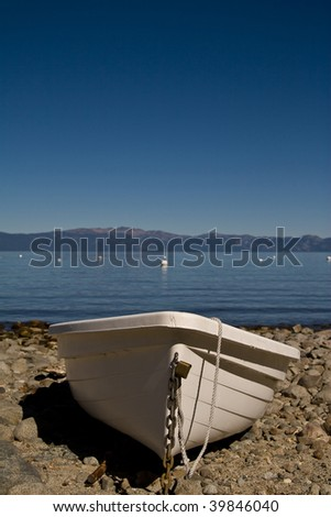 Single plastic boat beached on rocks, lake in background with mountains beyond - stock photo