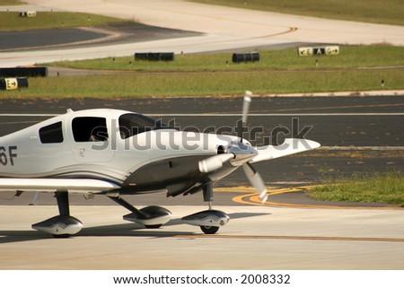 Single prop plane landing on runway - stock photo