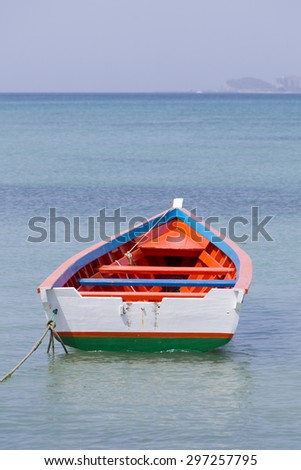 Single red and white wooden fisher boat alone in the bay of Pampatar Beach, Margarita Island. Venezuela - stock photo