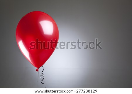 Single red balloon on a grey background  - stock photo