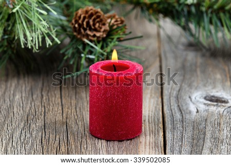 Single red candle with flame and evergreen setting on rustic wood. Selective focus on front part of candle and flame.    - stock photo