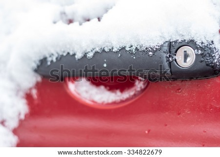 Single Red Car door handle covered in fresh snow. The key lock has been frozen shut. - stock photo