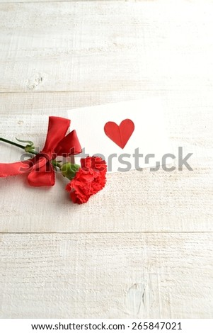 Single red carnation with message card - stock photo