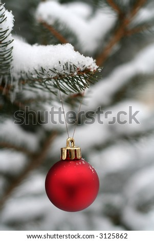 Single red Christmas ornament hung on a tree outside in the snow - stock photo