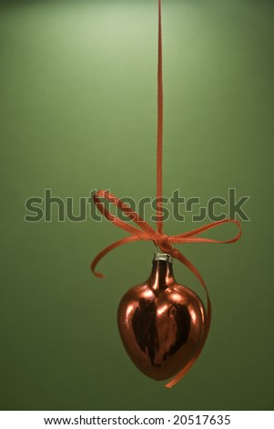 Single red heart ornament hanging isolated on green paper - stock photo