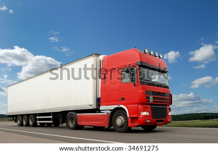 Single red lorry with white trailer over blue sky on the road. - stock photo