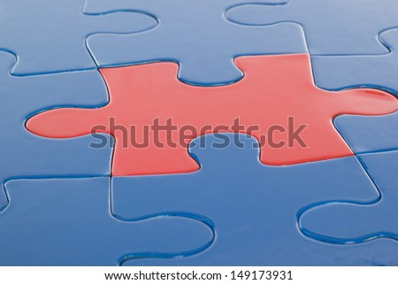 Single red piece in blue puzzle - stock photo