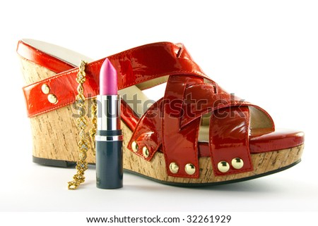 Single red shoe with pink lipstick and gold bracelet with clipping path on a white background - stock photo