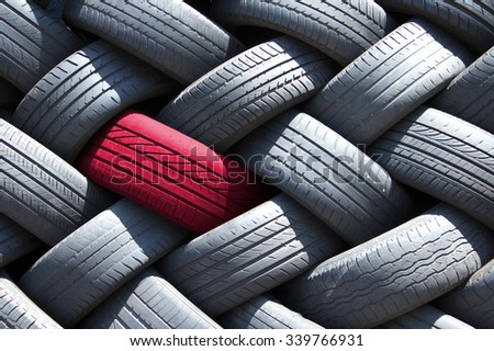 Single red tire in a stack of tires - stock photo