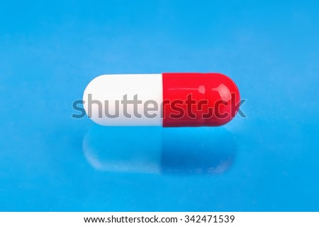 Single red white capsule close-up on a blue background - stock photo