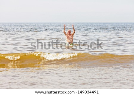Single retired senior man enjoying the refreshment of the sea on a hot summer day. Blue cloudy sky.