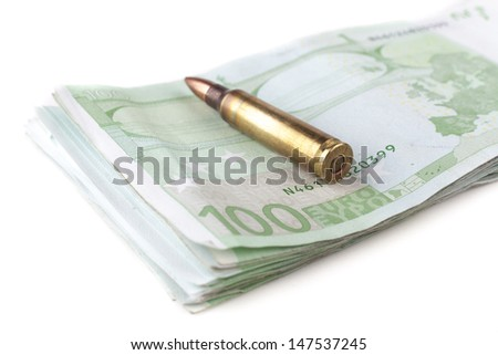 Single rifle bullet closeup with a pile of a hundred euro banknotes in the background isolated on white - stock photo