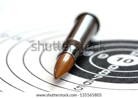 single rifle bullet on paper target for shooting practice - stock photo