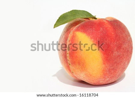 Single ripe peach with green leaves on white background - stock photo