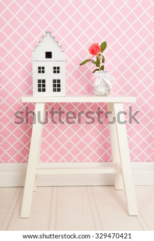 Single rose and decoration in pink interior - stock photo