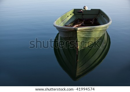 Single Row boat on Lake with Reflection in the Water - stock photo