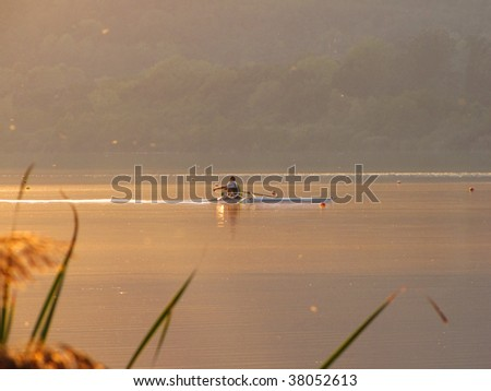 single rower during a tranquil sunset - stock photo