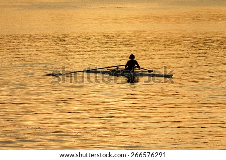 single rower in silhouette at sunrise