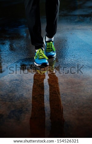 Single runner running in rain - stock photo