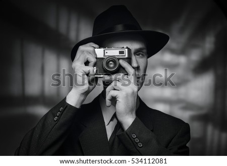 Single 1950s man in business suit and hat taking a picture over urban building background