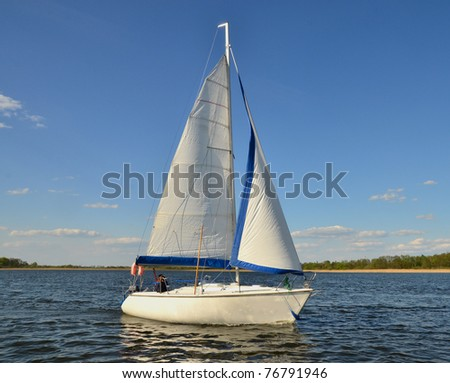 Single sail boat on the lake. People faces unrecognizable. - stock photo