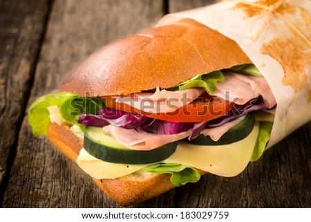 Single sandwich stuffed with cheese and ham  - stock photo
