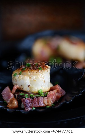 Single sauteed scallop with chives are pork largons in black scallop shells against a dark, rustic background. The perfect image for your fish restaurant menu cover design. Copy space.