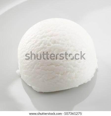 Single scoop of refreshing tangy sour lemon sorbet dessert on a white plate - stock photo
