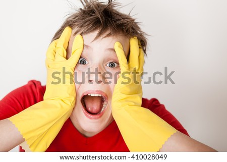 Single screaming child in red shirt and messy hair wearing yellow rubber gloves with hands on face next to copy space - stock photo